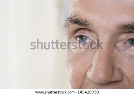 Detail portrait shot of a senior man's face against blurred background - stock photo