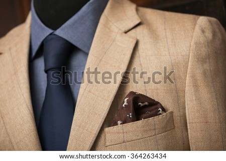 detail shot of a business shuit: blue shirt, navy tie and light brown coat