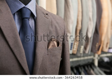 detail shot of a business suit: blue shirt, navy tie and brown coat; a lot of suits in the background