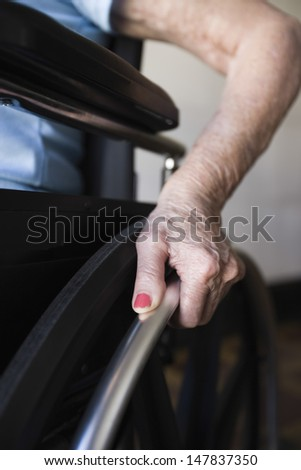 Detail shot of a woman operating wheelchair - stock photo