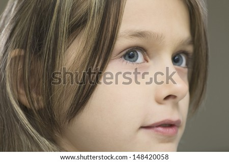 Detail shot of a young girl against gray background - stock photo
