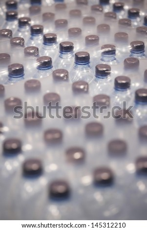 Detail shot of bottles of Water wrapped in plastic - stock photo