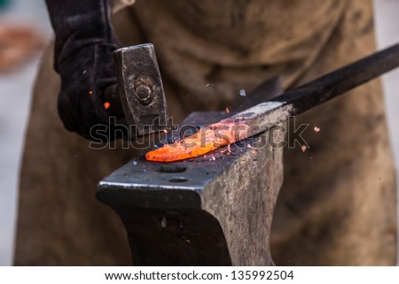 Detail shot of metal being worked at a blacksmith forge - stock photo