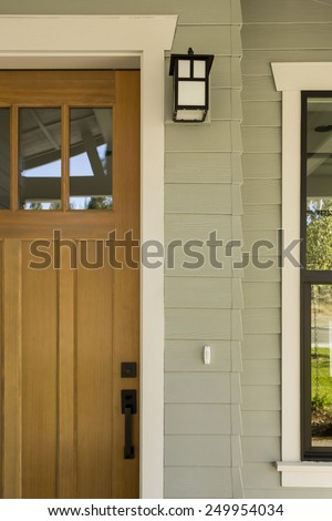 Detail Shot of Natural Wood Front Door with Surrounding White Door Frame, Porch Light, and Side Window - stock photo
