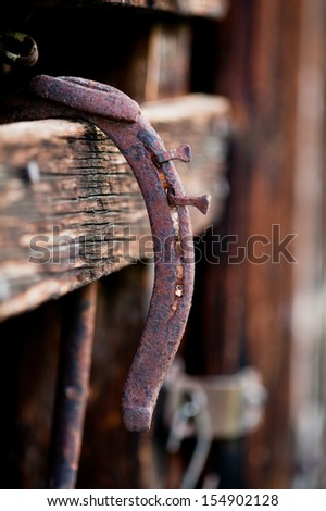 Detail shot showing the texture of an old, rusty, weathered horseshoe. - stock photo