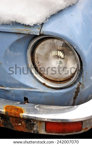 Detail shot with a headlight of an old car in winter time - stock photo