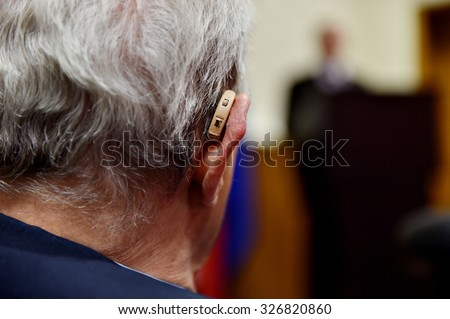 Detail shot with a hearing aid device used by old man during conference - stock photo