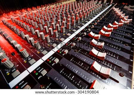 detail sound mixer in red and white light with great perspective - stock photo