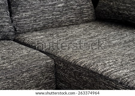 Detail to part of black and white cloth sofa - stock photo