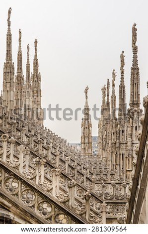 Detail vertical view of stone sculptures on roofs of Duomo Milano, Italy