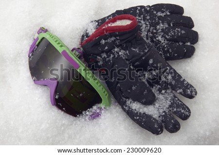 Detail view of a ski goggles and a pair of gloves in the snow - stock photo