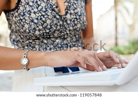Detail view of a young businesswoman's mid body section and hands typing on a laptop computer while sitting outdoors in a city.