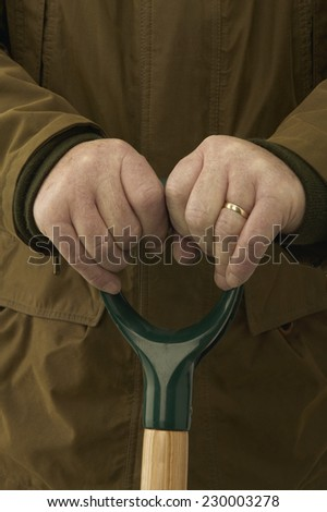 Detail view of an aging man using a shovel to dig - stock photo