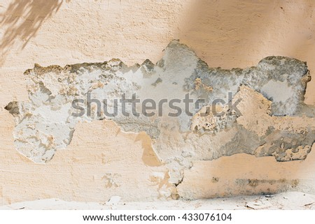 Detail view of crumbled and chipped tan colored plaster on neglected exterior wall