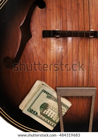 Detail view of old, beat-up acoustic guitar, with a wad of U.S. paper money stuck in the tailpiece.