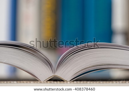 Detail view of open book in library. Shallow depth of field. Horizontal shot. - stock photo