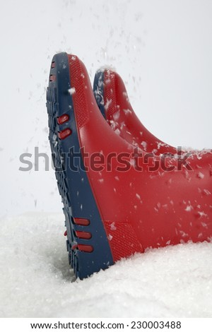Detail view of two boots in the snow - stock photo