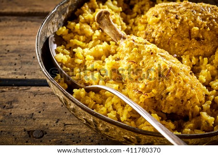 Detail view on steel pot and spoon with delicious and spicy chicken biryani drumstick and rice over wooden table - stock photo