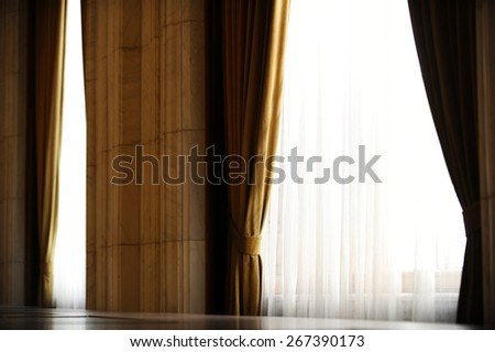 Detail with a yellow velvet window curtain shot against outdoor light