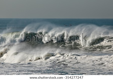 Detailed big sea wave breaking in a  beach from northern portuguese coast seeing a small fishing boat behind the wave