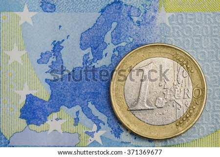 Detailed close up of an one euro coin on a blue twenty euro banknote with Europe map in background