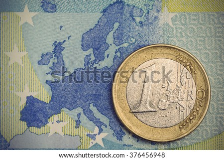 Detailed close up of an one euro coin on a blue twenty euro banknote with Europe map in background, Vintage filtered style  - stock photo