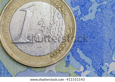 Detailed close up of an one euro coin on a twenty euro banknote