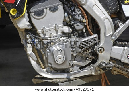 Detailed closeup of a four-stroke dirt bike engine isolated on black background.