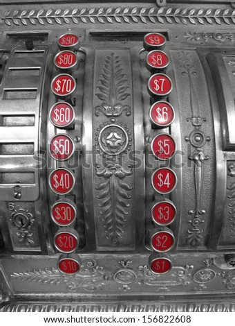 Detailed closeup of an old cash register with red number buttons for dollar amounts - stock photo