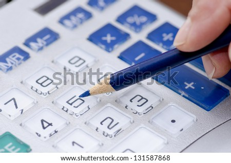 Detailed closeup of calculator display with hand, pencil and numbers. - stock photo