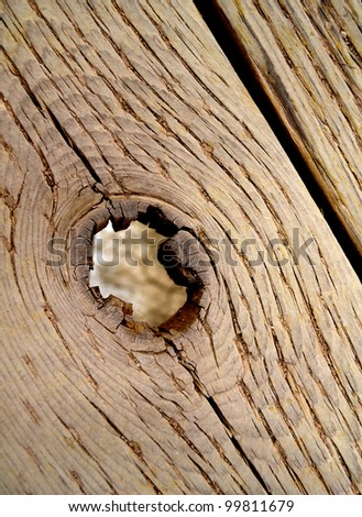 Detailed closeup of hole in old wooden bridge slat