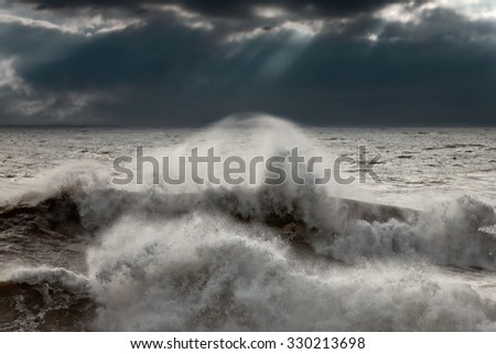 Detailed crashing wave against a dark sky with sunbeams before rain and storm. Portuguese coast. Enhanced sky. Focus on the wave. - stock photo
