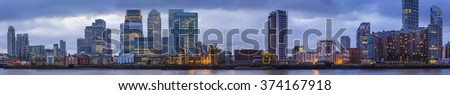 Detailed, high resolution panoramic photo about the skyscrapers of Canary Wharf at blue hour - London, UK - stock photo