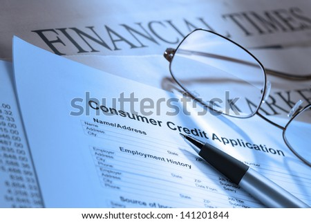 Detailed image of a consumer credit application form with pen and spectacles.