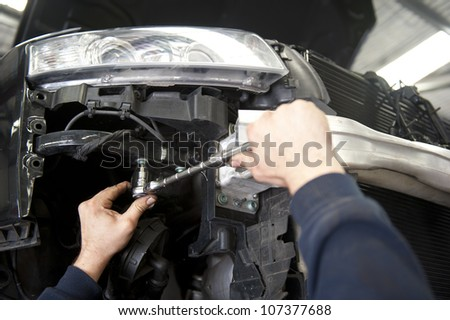 Detailed image of car repair, service and inspection by mechanic in auto garage. - stock photo