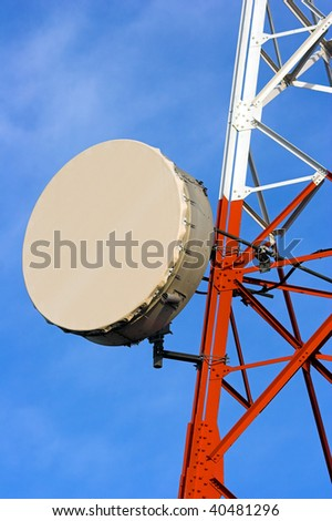 Detailed image of part of a red and white tower of communications with a telecommunication antenna against beautiful blue sky with clouds - stock photo