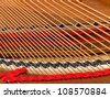 Detailed interior of grand piano showing the strings, pegs, sound board with focus close to the camera viewpoint - stock photo