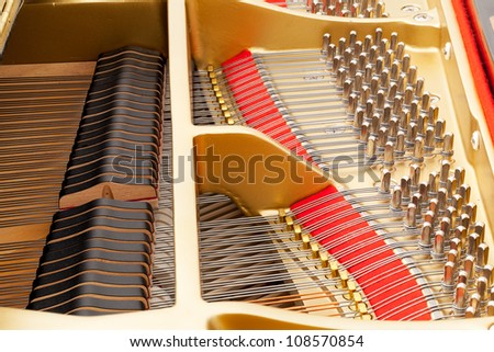 Detailed interior of grand piano showing the strings, pegs, sound board with focus sharp across image - stock photo