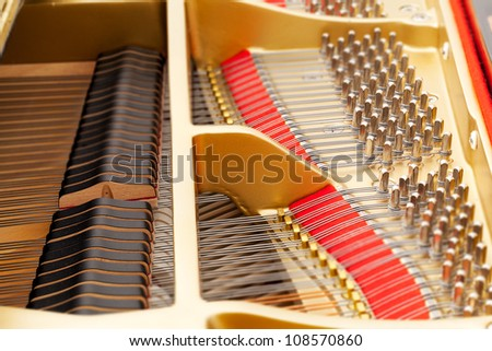 Detailed interior of grand piano showing the strings, pegs, sound board with focus sharp in one area - stock photo