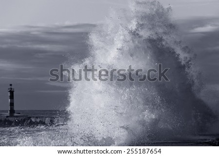 Detailed photo of a big breaking wave over a pier from the north of Portugal. Black and white toned blue. - stock photo