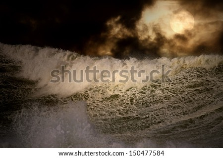 Detailed photo of a big stormy wave crashing over the coast at sunset - enhanced sky - stock photo