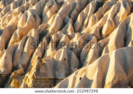 Detailed photo of vivid pink rock formations with caves from above in Cappadocia, Turkey - stock photo