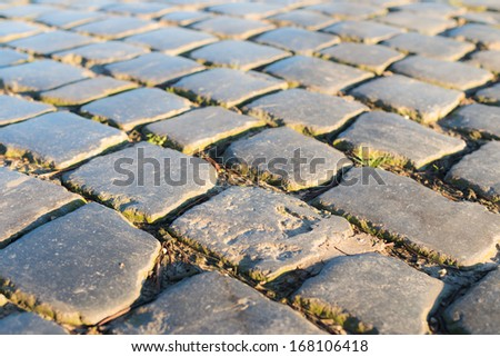 Detailed view at an old road paved with cobblestones on a sunny day. - stock photo