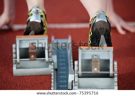 Detailed view of a female sprinter wearing sprinting shoes with spikes, leaving starting blocks - stock photo