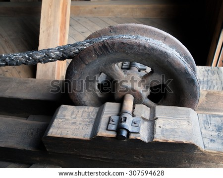 Detailed view of a rusty drag metal wheel as a part of pulley - stock photo