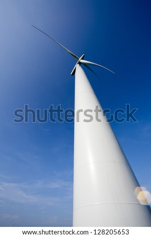 Detailed view of a wind turbine with clear sky in the background.
