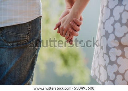 Detailed view of a young couple holding hands outdoor
