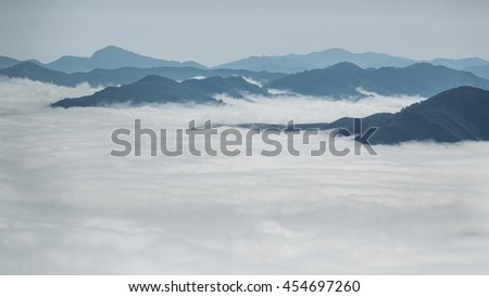 Detailed view of beautiful clouds and fog below mountain summits - stock photo
