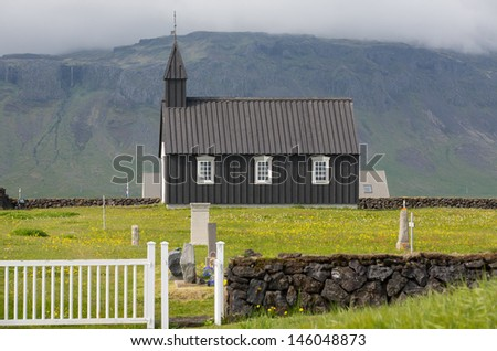 Detailed view of black wooden church in front of a mountain chain in Budir, Iceland