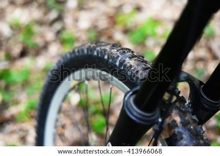 details bike front wheel axle disc brake damper  Downhill mountain bike. Mountainbiker rides in spring forest - stock photo
